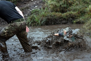 A mud run entrant emerges from a muddy water course at the 2018 Royal Marines Commando Challenge