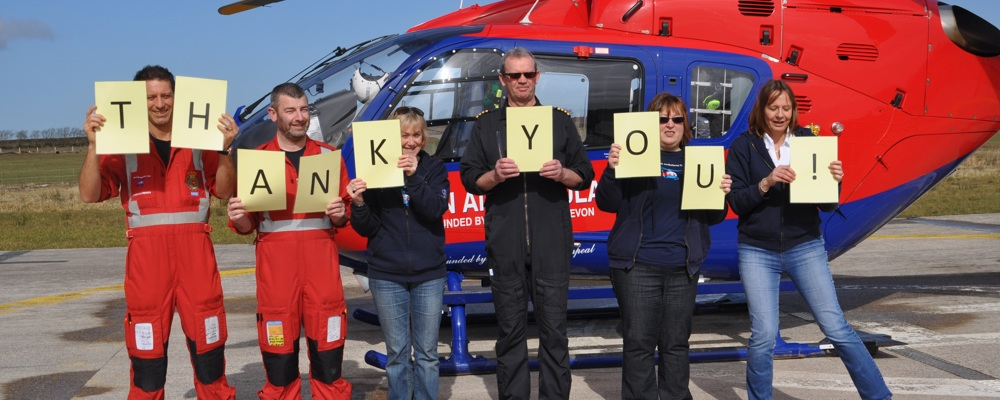 Members of our team hold the sign thank you next to a Devon Air Ambulance