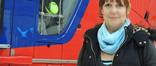 Patient, Kate Laubscher, next to one of our helicopters
