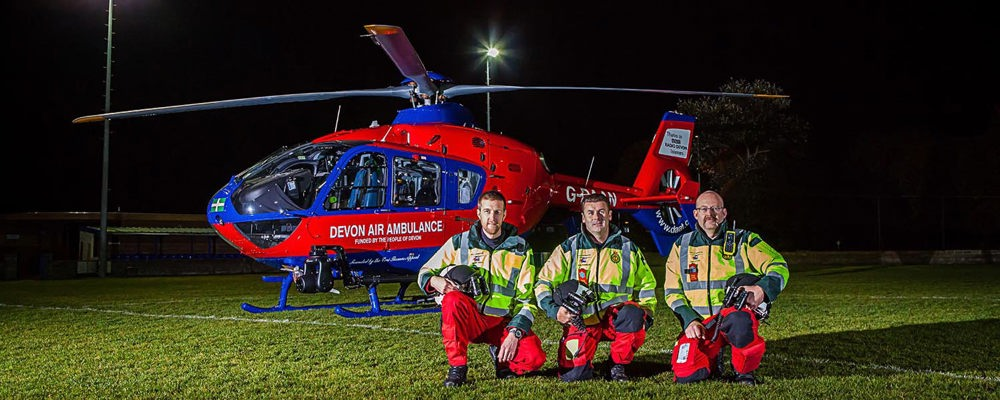 Our Air Ambulance Crew crouch by one of our helicopters at a floodlit community landing site during hours of darkness.