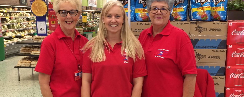 Cara Jones and volunteers at a supermarket stand.
