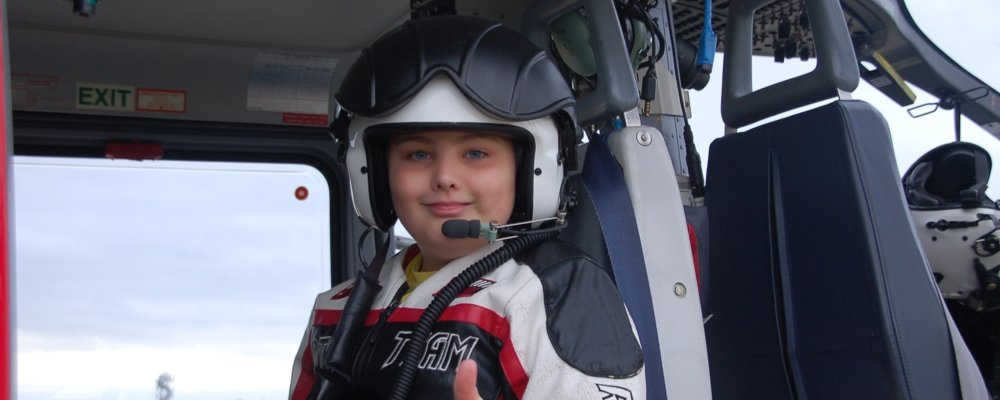 child patient in helicopter giving the thumbs up