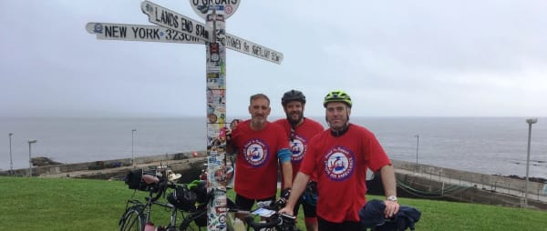 Fundraising cyclists pose at John O Groats  sign