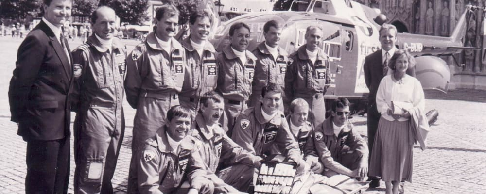 Our founder, Ann Thomas, stands with the Devon Air Ambulance crew with the Helicopter in August 1992.