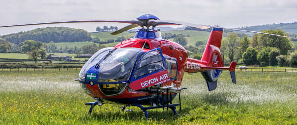 Devon Air Ambulance helicopter in a meadow awaits its patient