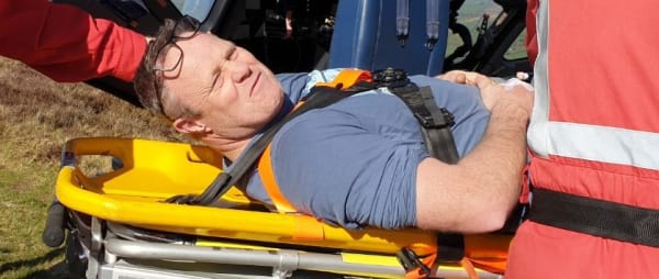 Paraglider, Clive, in a stretcher as he is attended to by Devon Air Ambulance