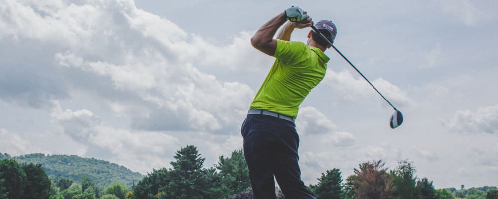 man swinging golf club against sky background