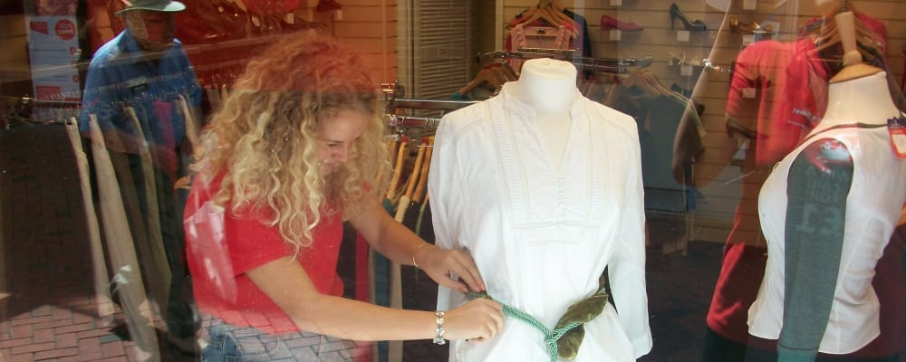 A young volunteer dresses the window in one of our charity shops