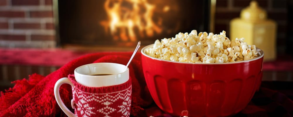 A mug of hit chocolate and a bowl of popcorn in front of an open fire